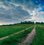 Beautiful sunrise over misty meadow and rural road Stock Image