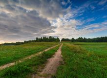 Beautiful sunrise over misty meadow and rural road Stock Images