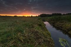 Beautiful sunrise over misty meadow and stream Royalty Free Stock Photo