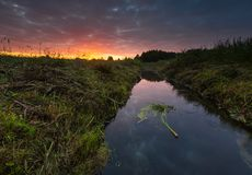 Beautiful sunrise over misty meadow and stream Stock Photography