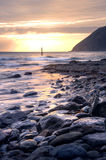 Beautiful sunrise over ocean with cliffs and rocks Stock Photo