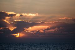 Beautiful sunrise over an ocean horizon. Dawn at sea. Orange anticrepuscular rays as sun is emerging from behind autumnal clouds Stock Photography