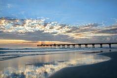 Beautiful sunrise over ocean horizon and pier. Sun rising over horizon and pier, beach illuminated with sunlight, beautiful sky reflected on the beach Stock Photos