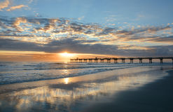 Beautiful sunrise over ocean horizon and pier. Sun rising over horizon and pier, beach illuminated with sunlight, beautiful sky reflected on the beach Stock Photo