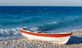 Beautiful sunrise over an old wooden fishing boat on a pebble beach in Greece Rhodes stock photos