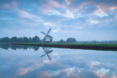 Beautiful sunrise over river and windmill Royalty Free Stock Images