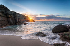 Beautiful Sunrise over a sandy cove. Sunrise at Porthgwarra Cove on the Lands End Peninsula in Cornwall Royalty Free Stock Images