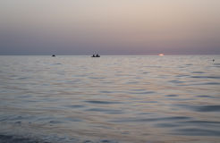 Beautiful sunrise over the sea, the fishermen in a boat Stock Image