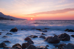A beautiful sunrise over the sea. In the foreground large stones Stock Photography