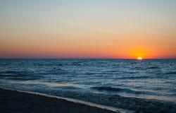 Beautiful dawn, red sun, purple pink sky, clear sky, sunrise over the sea, blue sea, waves Stock Images