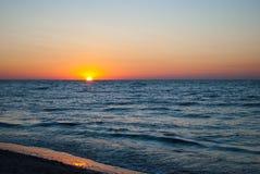 Beautiful dawn, red sun, purple pink sky, clear sky, sunrise over the sea, blue sea, waves Stock Image