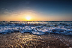 Beautiful sunrise over the sea. Shining waves Stock Photography