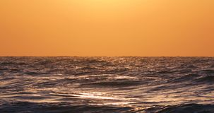 Beautiful sunrise over the sea and splashing waves on the beach. Video stock footage