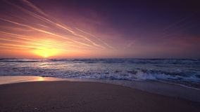Beautiful sunrise over the sea and splashing waves on the beach. Video stock video footage