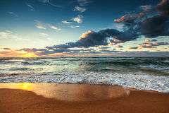 Beautiful sunrise over the sea. Waves crashing onto the shore Stock Images