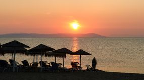 Beautiful Sunrise Over the Sea and a Woman on the Beach Nea Vra. Sna, Greece Royalty Free Stock Image