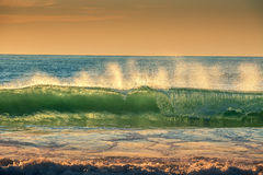 Beautiful sunrise over the splashing sea waves Stock Photo