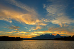 Beautiful sunrise over volcanoes Kluchevskaya group with reflection in the river Kamchatka. Stock Photos