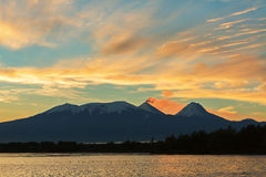 Beautiful sunrise over volcanoes Kluchevskaya group with reflection in the river Kamchatka. Royalty Free Stock Images