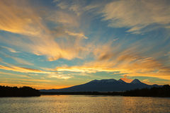 Beautiful sunrise over volcanoes Kluchevskaya group with reflection in the river Kamchatka. Stock Photo