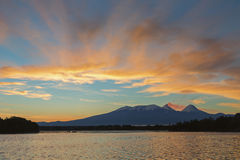 Beautiful sunrise over volcanoes Kluchevskaya group with reflection in the river Kamchatka. Stock Photography