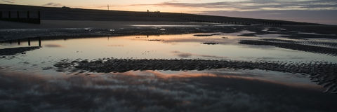 Beautiful sunrise panorama landscape reflected in pools on beach Royalty Free Stock Photos