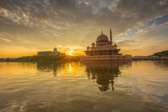 Beautiful sunrise at Putra Mosque, Putrajaya Malaysia. Colorful sunrise clouds, sunburst between the building and reflection at the lake surface stock photography