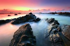 Beautiful sunrise at rocky beach. Sunrise at Pandak Beach, Terengganu Royalty Free Stock Image