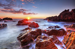 Beautiful sunrise on rocky shore Royalty Free Stock Images