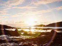 Beautiful sunrise on rocky shore and dramatic sky clouds. Reflection and  flare Stock Photo