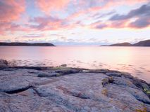 Beautiful sunrise on rocky shore and dramatic sky clouds. Reflection and flare stock image