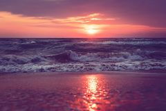 A beautiful sunrise on Sanibel Island Florida. Bright intense pink purple orange sunrise at the sea. Waves at dawn. reflection of sunlight in water and sand on royalty free stock images