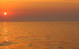 Beautiful sunrise on sea with purple sky andgolden reflection of sun in water with copy space. Summer vacation. Royalty Free Stock Images