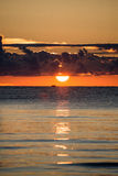 Beautiful sunrise in the sea at the wild beach Stock Photos