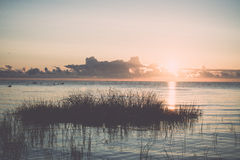 Beautiful sunrise in the sea at the wild beach. Vintage. Stock Photography