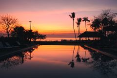 Beautiful Sunrise with silhouette coconut palm tree and swimming pool in beautiful luxury hotel resort. In dramatic color contrast Royalty Free Stock Image