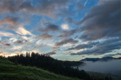 Beautiful sunrise sky and clouds over the silhouette of a coniferous forest stock photos