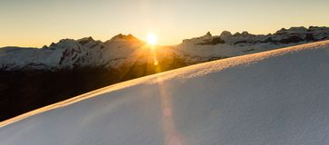 Beautiful sunrise in snowy mountain landscape. Sunbeams illuminating unspoiled powder snow. Alps, Switzerland. Amazing winter sunrise in Swiss Alps. Sunlight royalty free stock images