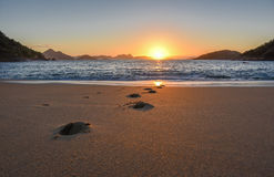 Beautiful sunrise, solar path on water and footprints at the deserted Praia Vermelha Beach Royalty Free Stock Images