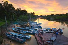 Beautiful sunrise on a tropical river. Old rustic local boats stock images