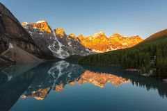Moraine lake in Banff National Park, Canada. Beautiful sunrise under turquoise waters of the Moraine lake with snow-covered peaks above it in Banff National royalty free stock images