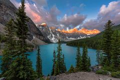 Moraine lake in Banff National Park, Canada. Beautiful sunrise under turquoise waters of the Moraine lake with snow-covered peaks above it in Banff National royalty free stock image