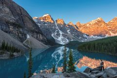 Sunrise at Moraine lake in Canada. Beautiful sunrise under turquoise waters of the Moraine lake with snow-covered peaks above it in Canadian Rockies,  Banff Royalty Free Stock Photography