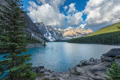 Moraine lake in Canada. Beautiful sunrise under turquoise waters of the Moraine lake with snow-covered peaks above it in Canadian Rockies,  Banff National Park Stock Photo