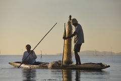 Beautiful sunrise. An unidentified people on boat at the lake with net fishing Royalty Free Stock Photos