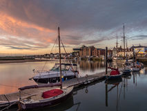 Beautiful Sunrise at Wells Harbour Norfolk. Sunrise lighting up boat moorings and the town at high tide. Wells-next-the-Sea Norfolk royalty free stock photos