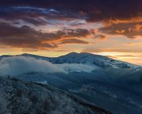 Beautiful sunrise in the winter mountains. Dramatic cloudy over sky. stock photo
