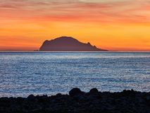 Beautiful sunrise withe the Panarea island seen from the Salina island in the Aeolian islands, Sicily, Italy.  Stock Photo