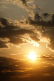Beautiful sunset. A yellow sunrise sky with the sun, clouds and sunbeams Royalty Free Stock Photo