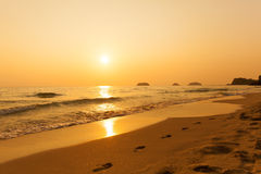 Beautiful sunset above the sea. Footprints in the sand. Royalty Free Stock Image